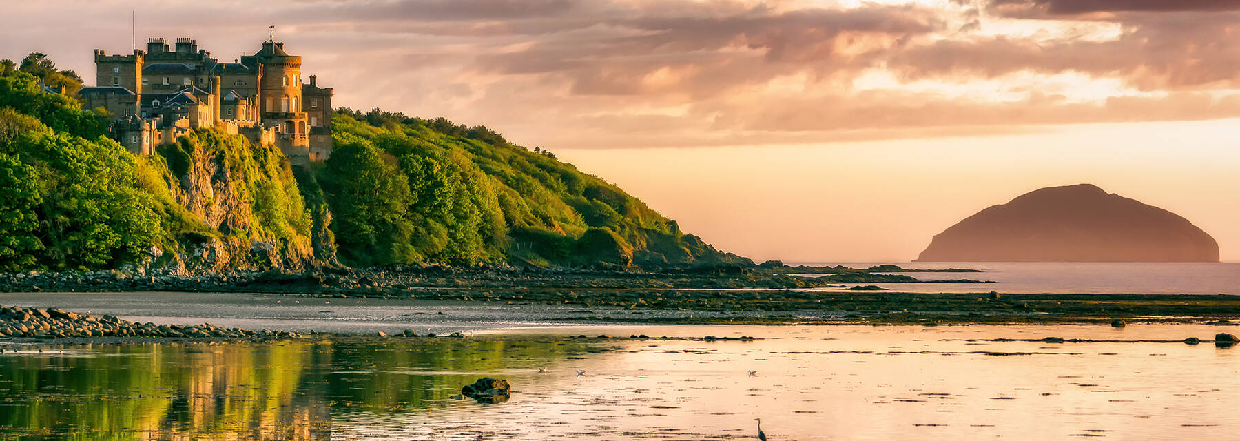 Culzean Castle seen from the beach as the sun sets. A heron stands on the foreshore. The silhouette of Ailsa Craig can also be seen in the Firth of Clyde.