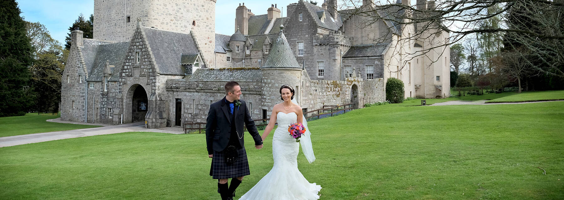 Wedding couple walking across a lawn in front of Drum Castle