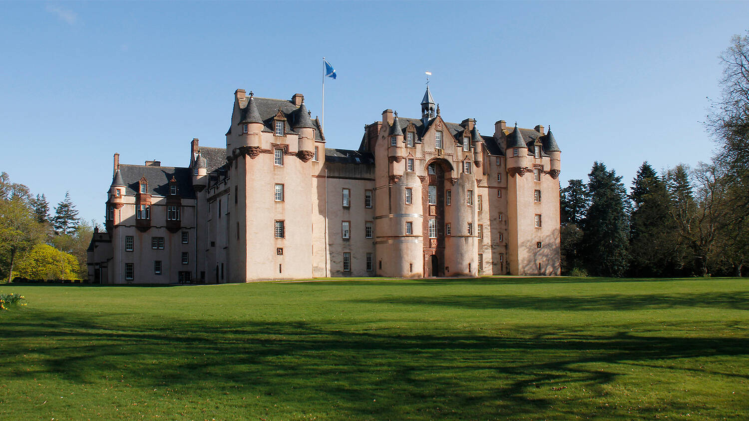 An exterior view of Fyvie Castle, seen from the lawn on a sunny day. Tall trees can be seen in the background behind the castle.