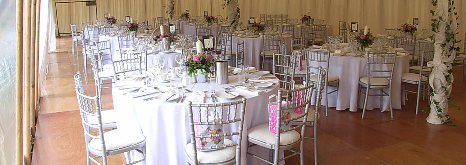 The interior of a marquee, set up for a wedding meal