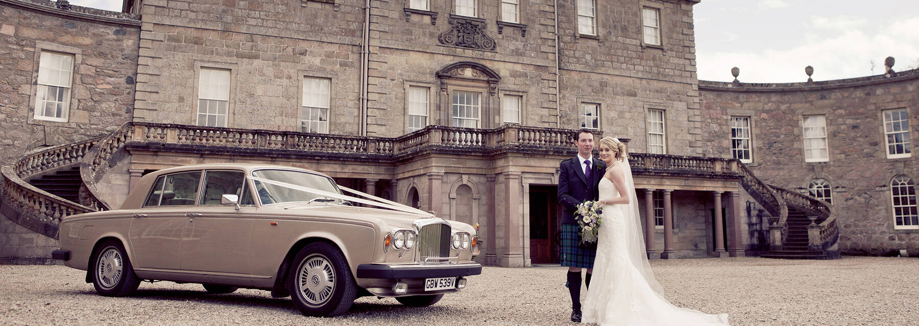 A black and white photo of a wedding couple standing beside their wedding car in front of Haddo House