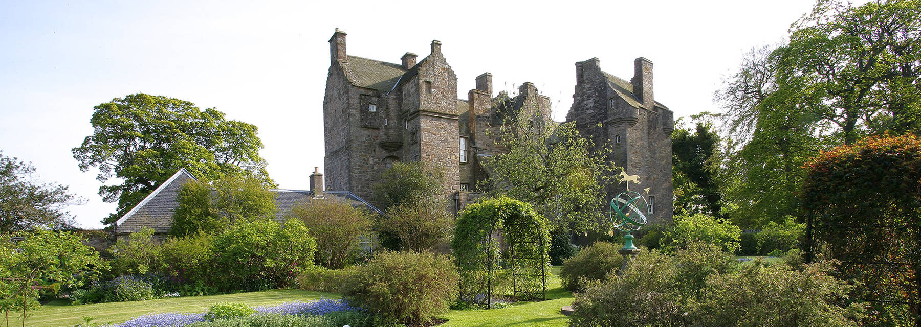 A view of Kellie Castle with its towers and chimneys, seen from a colourful garden. The bed in the foreground is filled with small blue flowers, mirroring the sky!