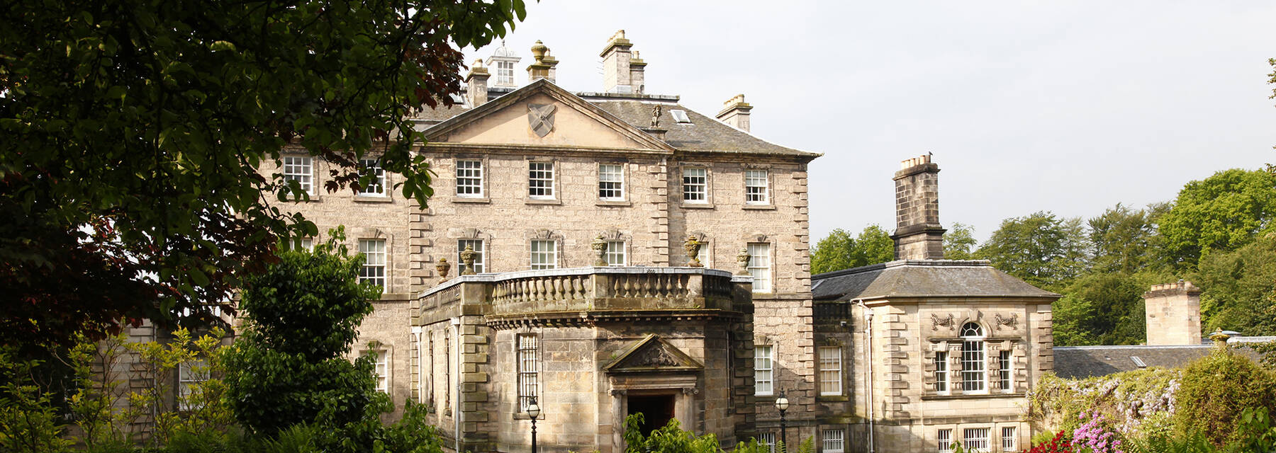 A view of the entrance to Pollok House, seen from the surrounding woodland.