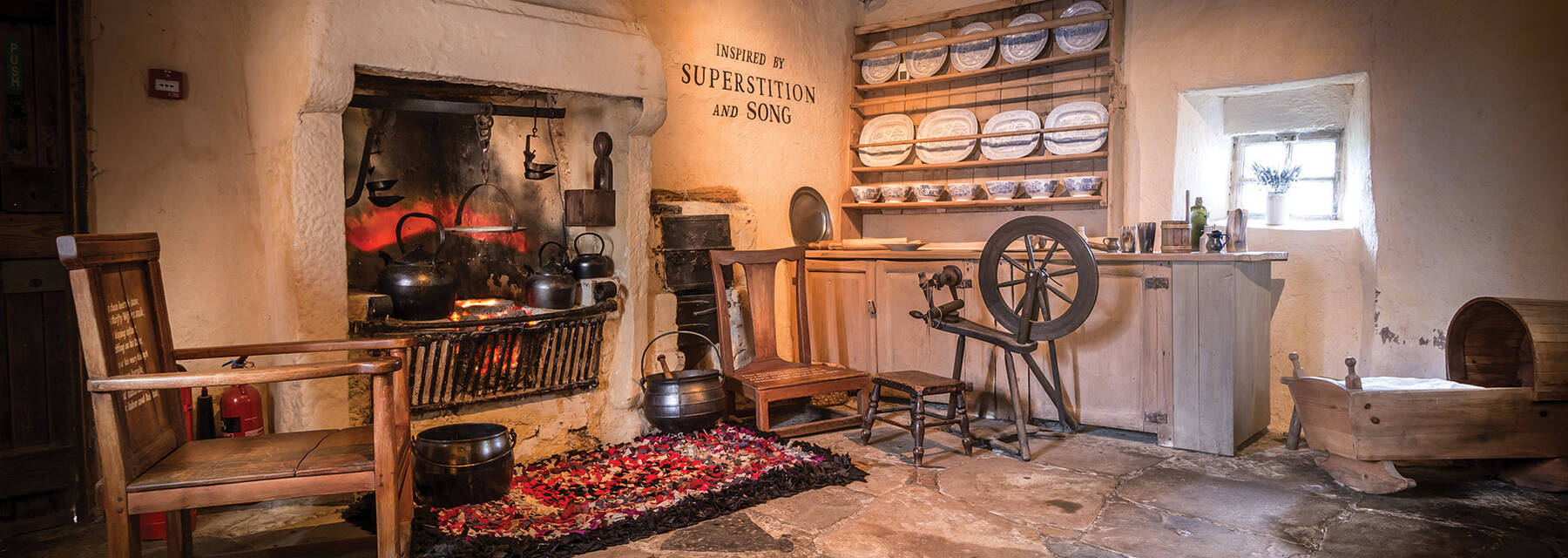 A view of the kitchen showing the hearth and spinning wheel in Burns Cottage.