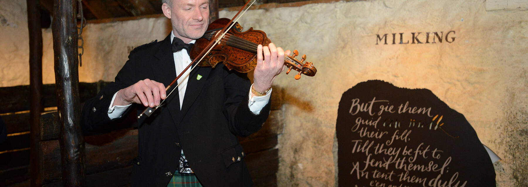 A fiddler playing at Burns Cottage for a Burns Supper