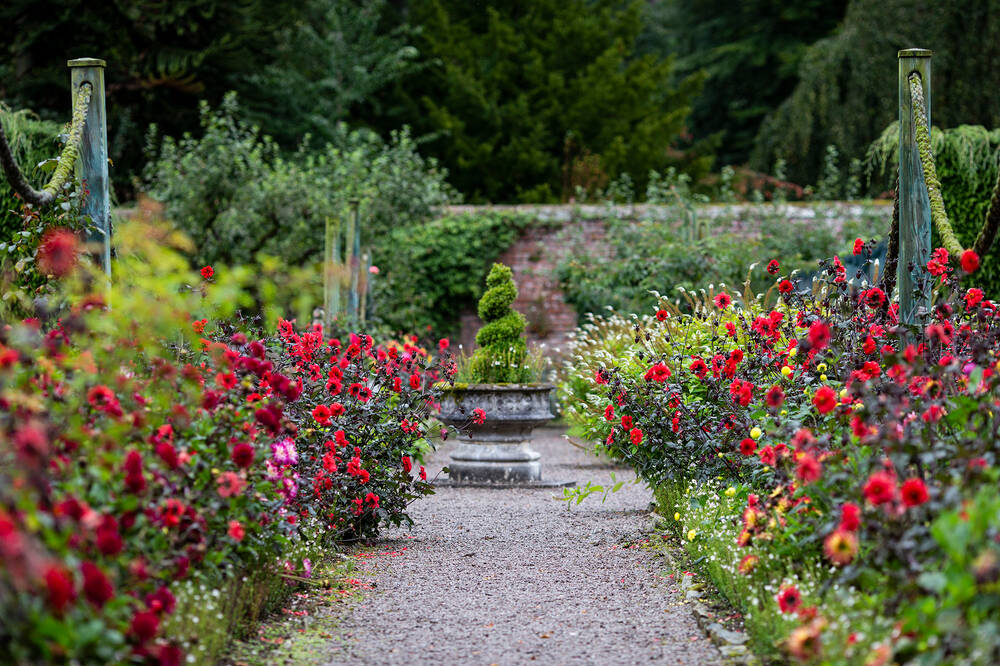 A gravel path leads through a walled garden towards an urn. Colourful flowerbeds line the path.