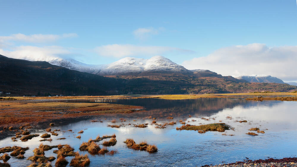 A view across  Loch Torridon on a bright winter day, looking towards the snow-covered mountains in the distance.