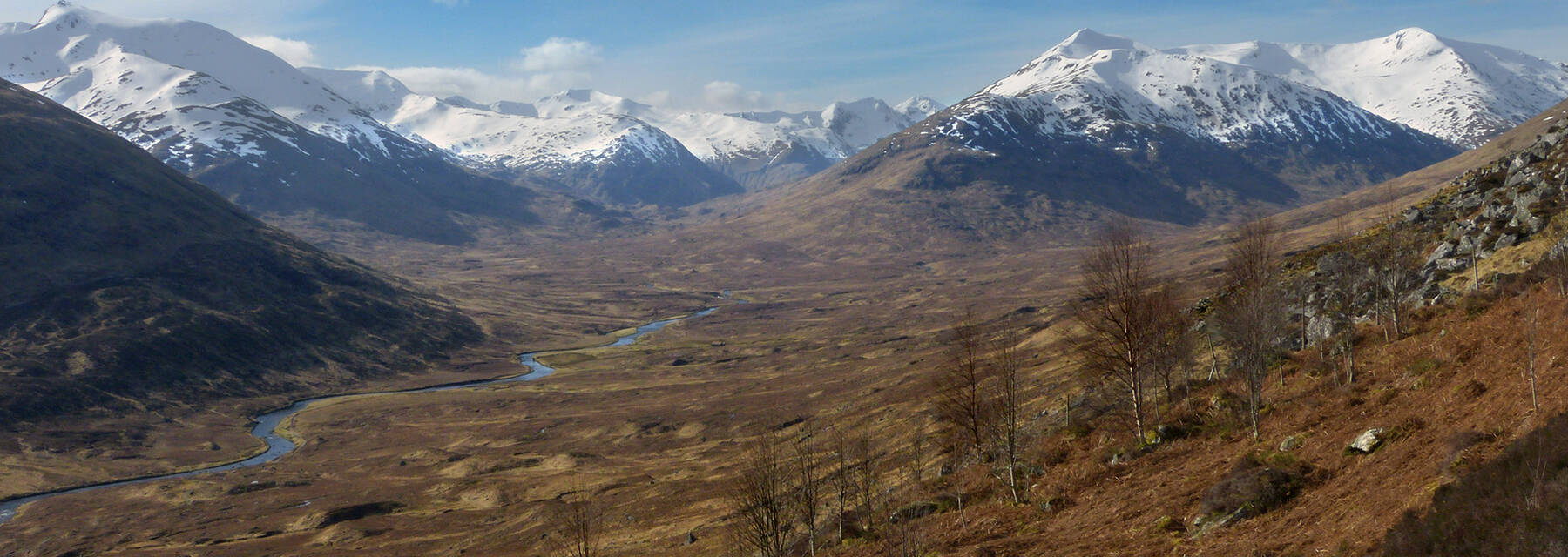 In the background are the West Affric snow-capped mountains. In the foreground is a hillside, with occasional bare trees. A river snakes through the glen to the left of the image.