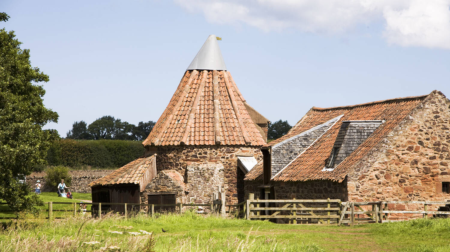 Preston Mill is surrounded by grass meadows. It has orange stone walls with a conical roof, that leans slightly to the side.