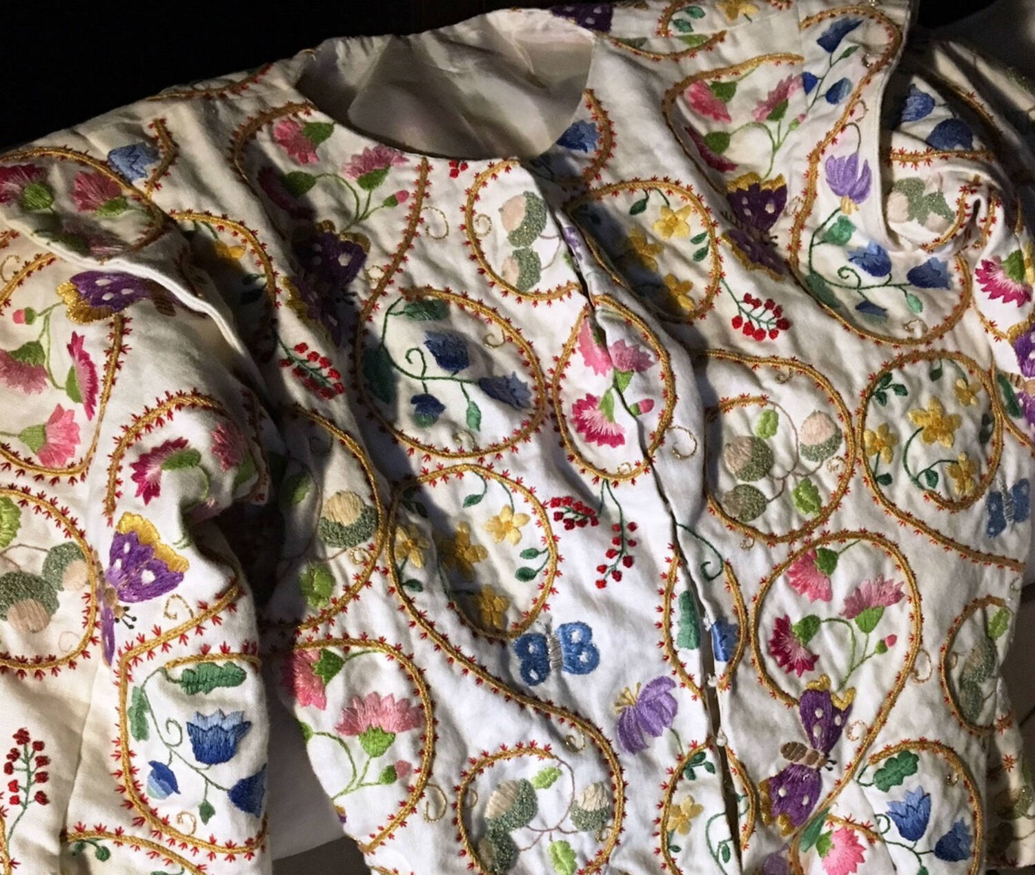 A detail of the crewelwork lady's jacket