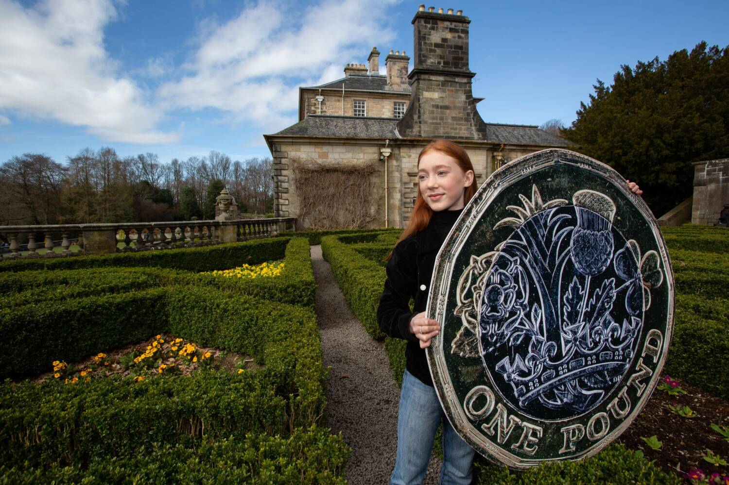 Cherry stands in the parterre garden at Pollok House holding a giant pound coin.