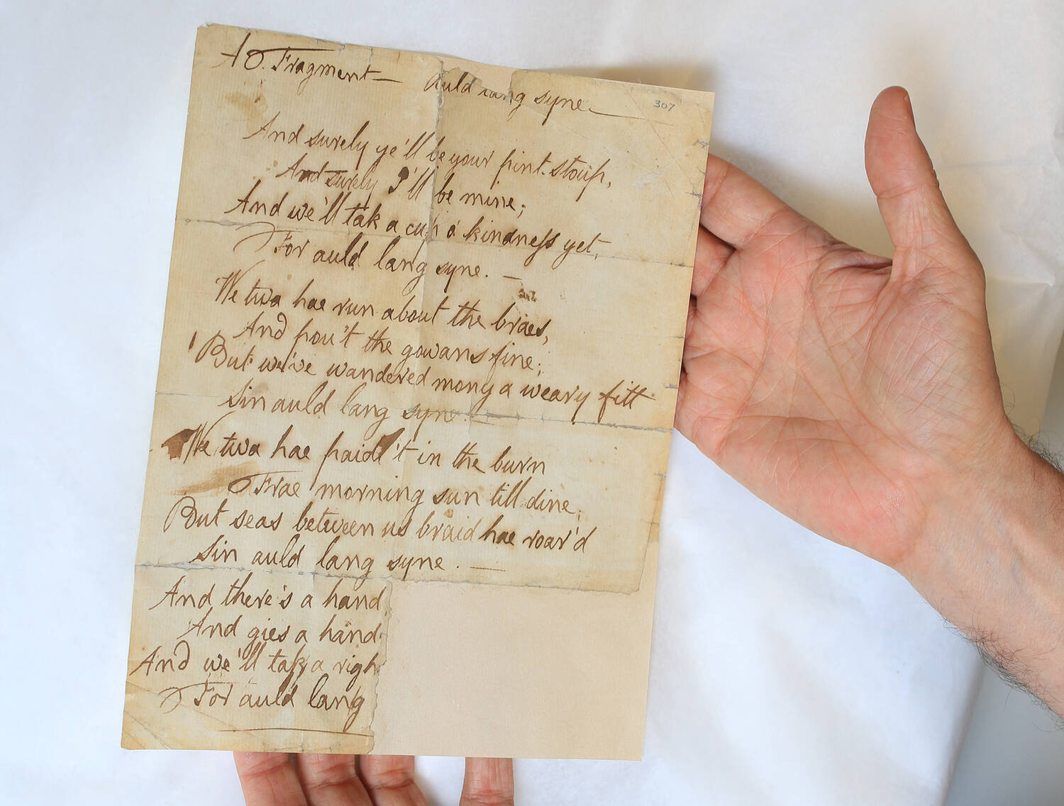 Two hands hold out a page of Burns's handwritten manuscript for 'Auld lang syne'.