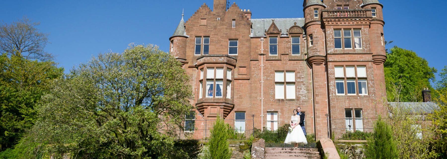 Threave House seen from the garden, with a bride and groom standing on the steps