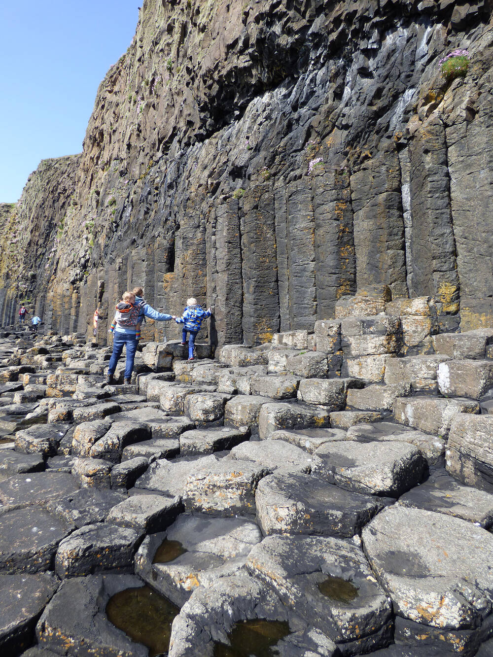 Family walking along the rocks to Fingal's Cave