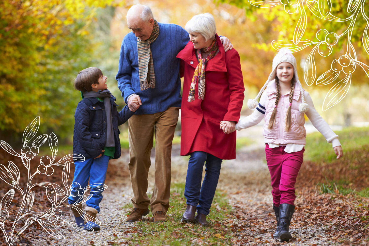 Two grandparents and their two grandchildren walk along a woodland path in autumn. They are smiling and holding hands with each other.