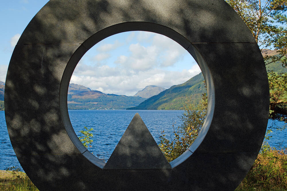 Loch Lomond and mountains in the distance, seen through the centre of the Ben Lomond Memorial sculpture. The sculpture is a granite ring, with a triangle shape at the bottom.