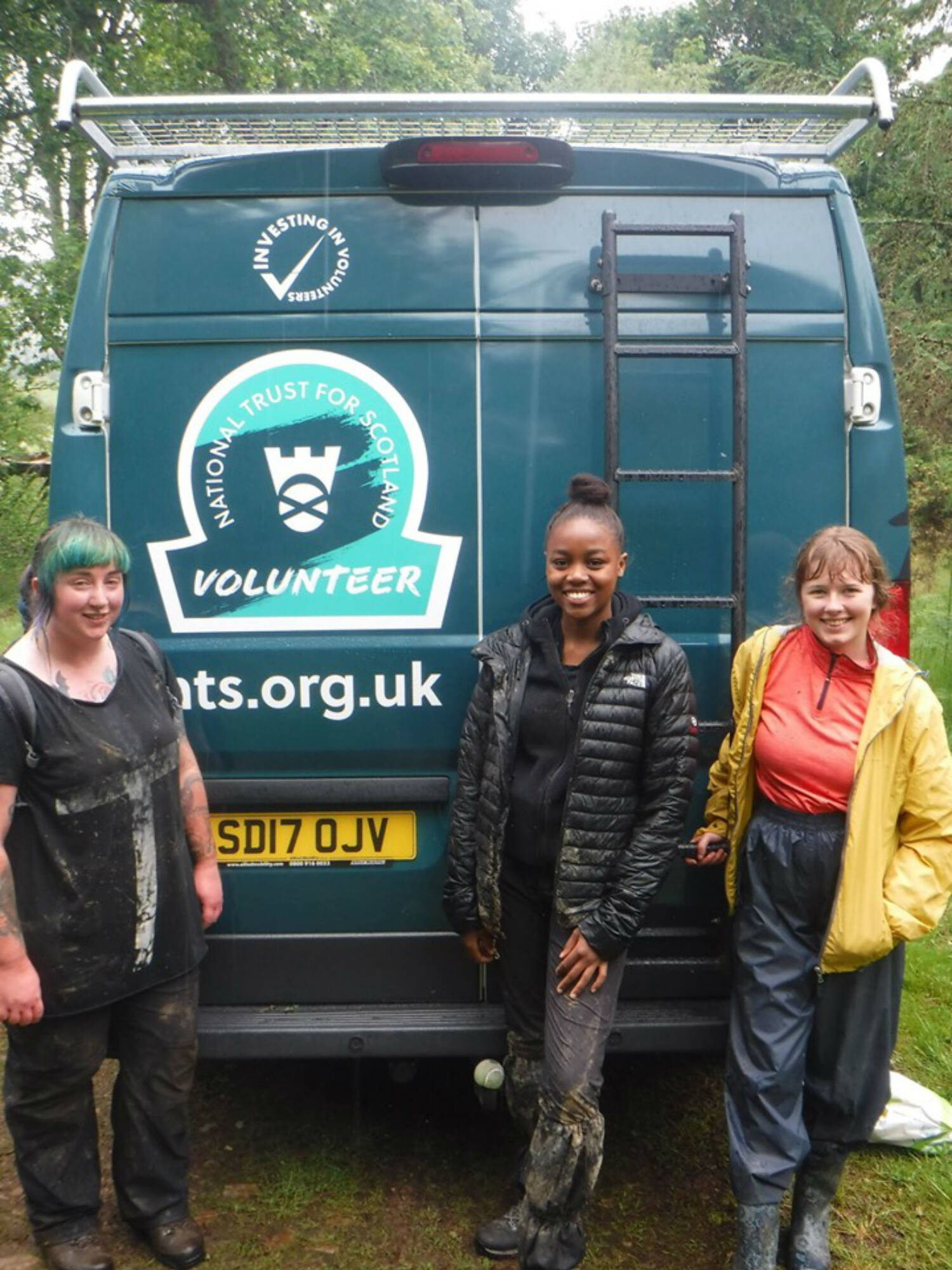 Three women stand with a National Trust for Scotland omega sign at the back of a van