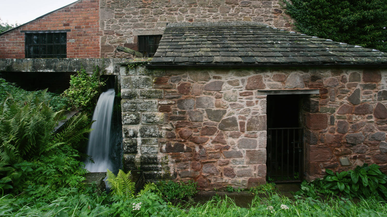 The exterior of the stone Barry Mill with the millrace outflow pouring out at the side.