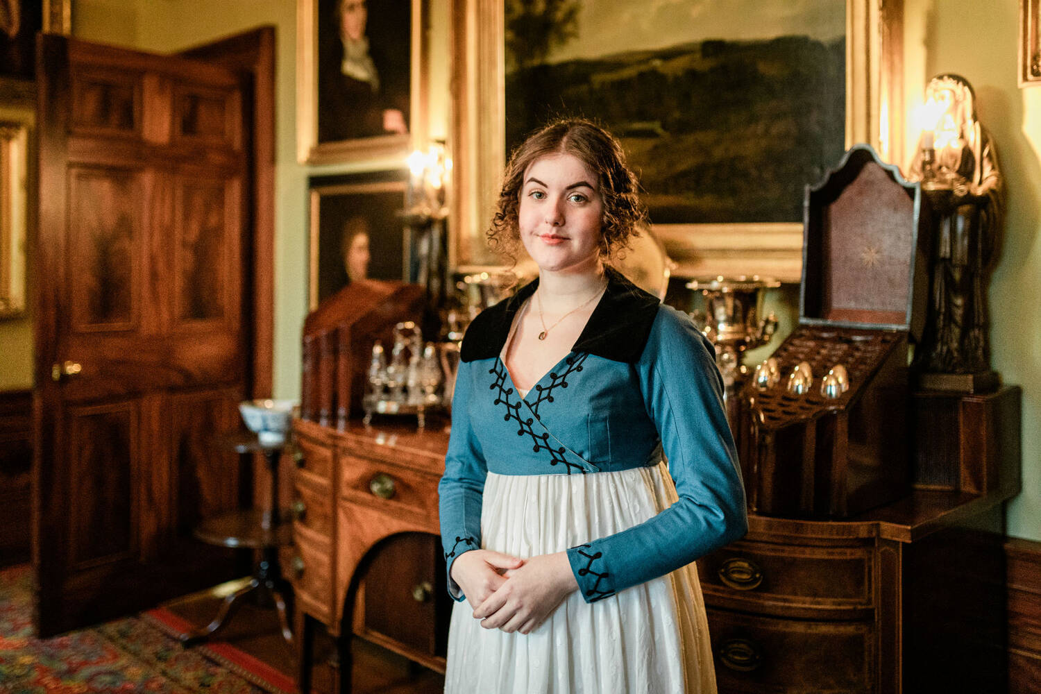 Woman in period costume in a rooms with paintings lining the walls