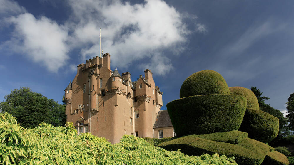 A view of Crathes Castle from the garden, with the yew topiary hedges in the foreground. It's a lovely sunny day.