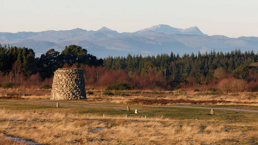 A view of Culloden Battlefield, looking towards the memorial cairn and with hills in the distance.