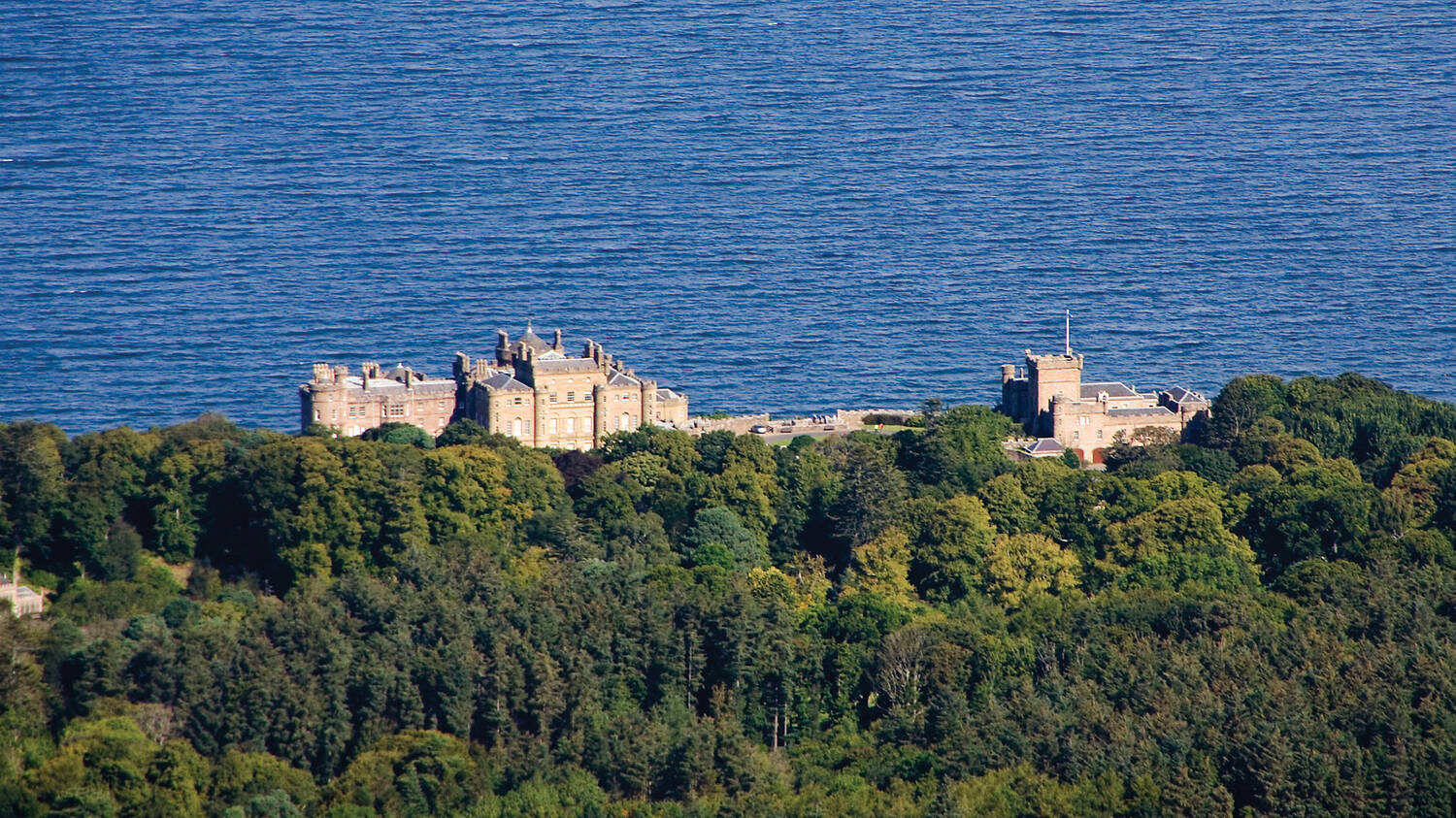 A view of Culzean Castle, seen from the air, looking towards the sea with woodland in the foreground.
