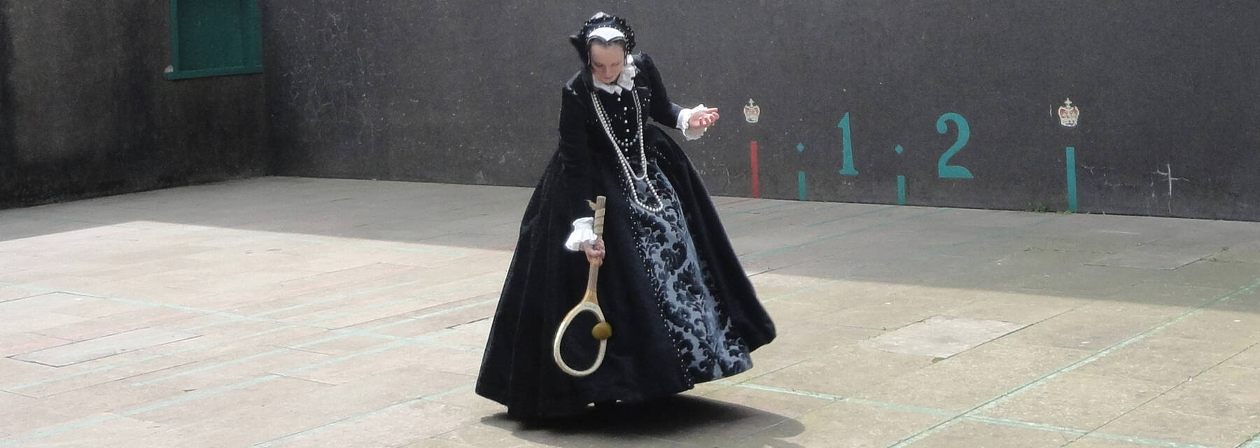 Woman in Renaissance costume playing tennis in Falkland Palace court