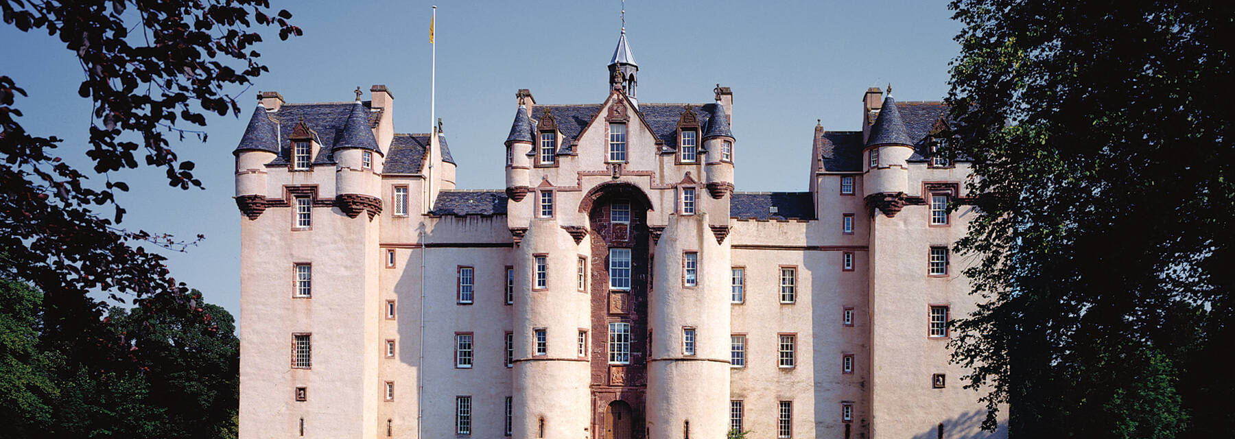 A view of the front of Fyvie Castle, showing its numerous towers, seen from the lawn. Large trees frame the shot.