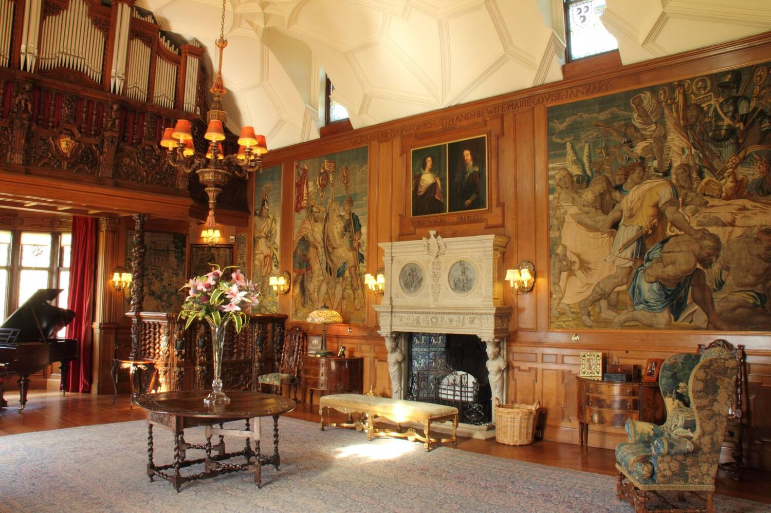 Grand room in a castle, with a large stone fireplace on a wood-panelled wall. There is a grand piano next to the window at one end of the room, and paintings and tapestries on the wall.