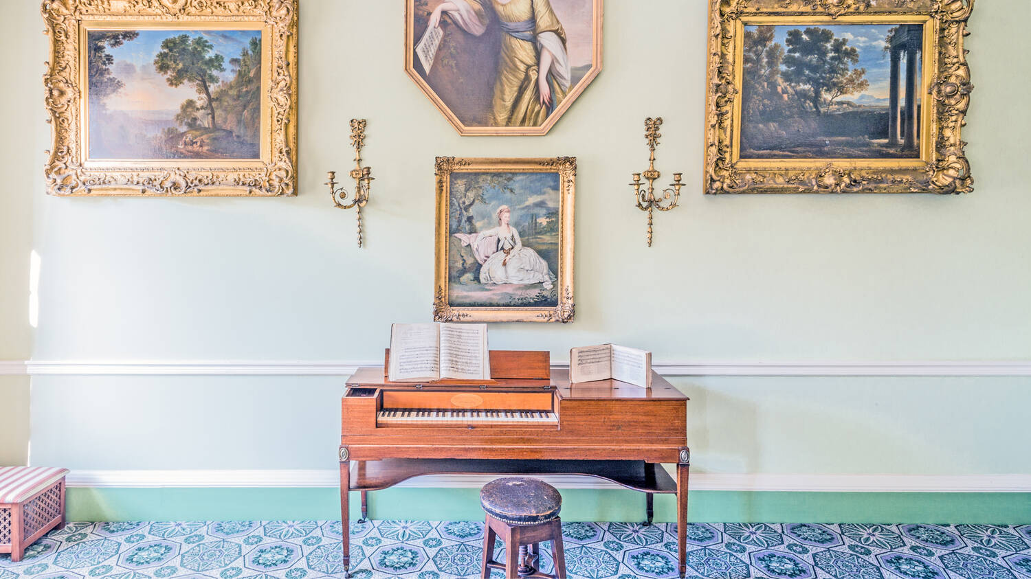 A wooden harpsichord stands in a grand drawing room, with gilt-framed paintings on the wall behind. A stool sits before the harpsichord and sheet music rests on top.