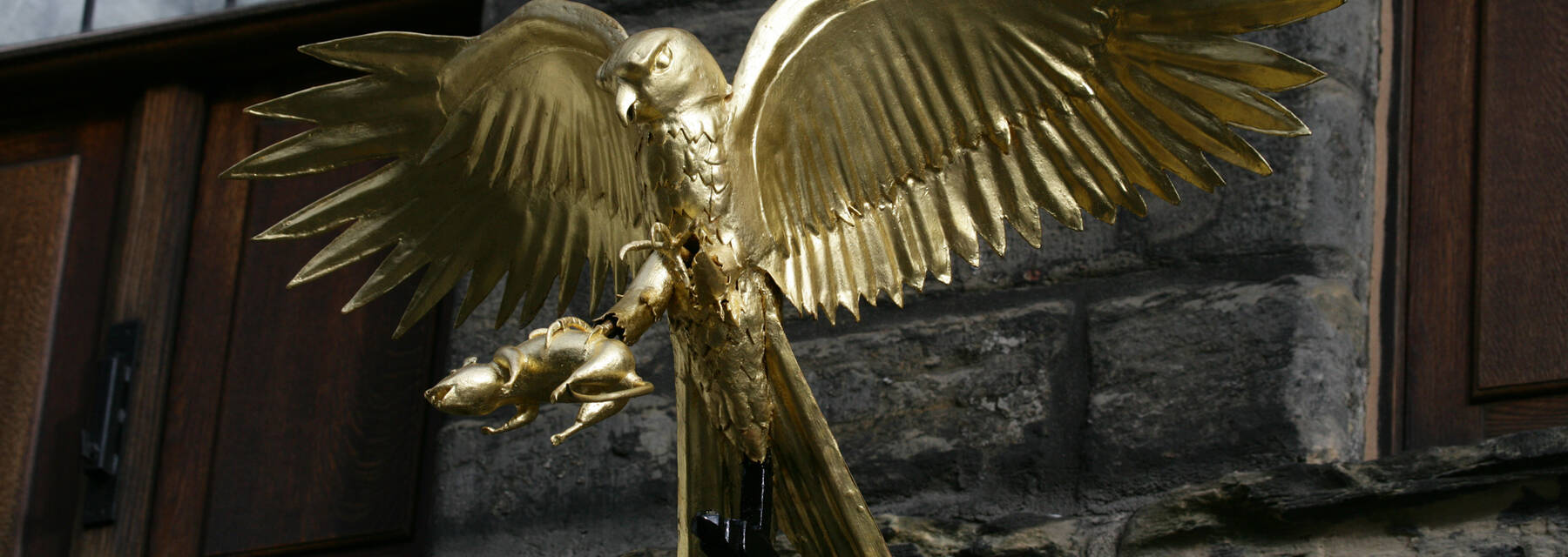 Gladstone's Land exterior wall close up of golden sculpture of a bird of prey clutching a rodent