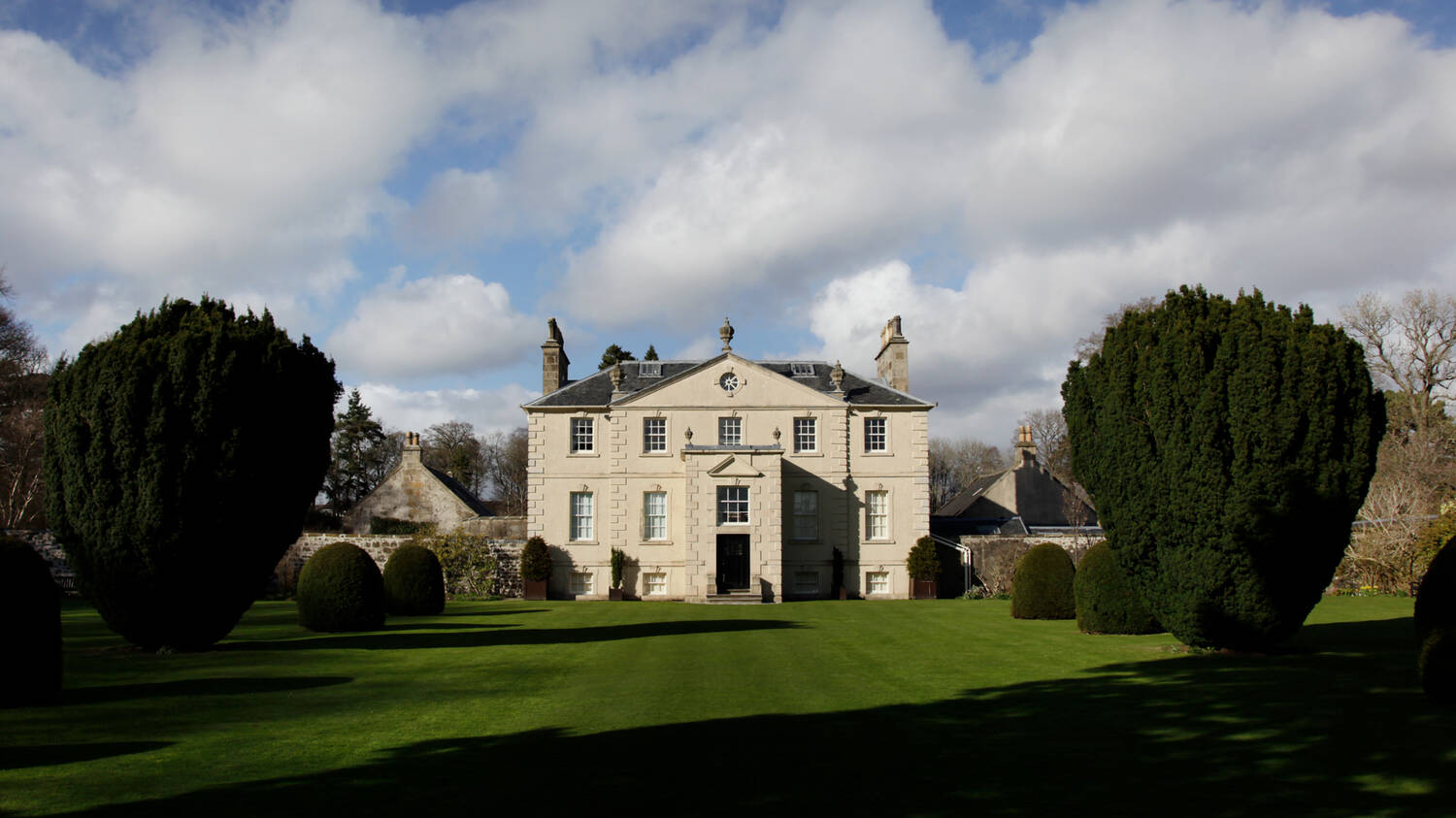 A symmetrical, Georgian-style large country house stands at the top of an immaculate lawn, with large yew trees to either side. It is a sunny day with fluffy white clouds across a blue sky.