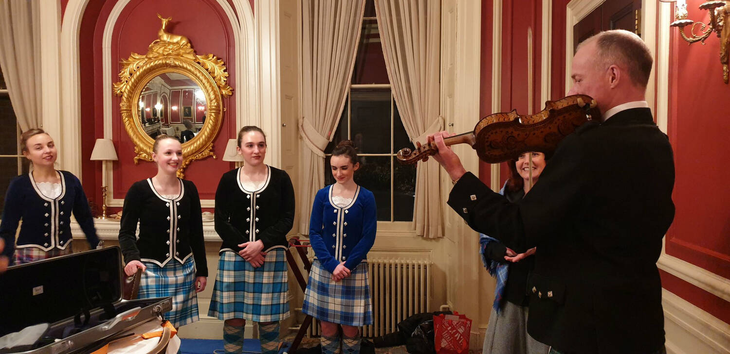 A man plays a violin, in front of 5 people wearing Highland dance outfits