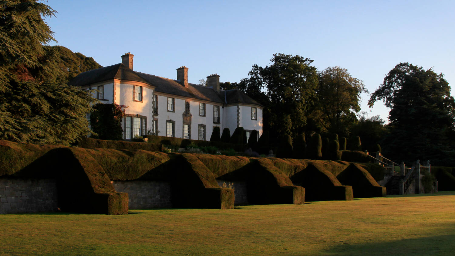 Hill of Tarvit seen from the lawns below on a sunny day. Manicured yew hedges define the terraces leading up to the house, which is surrounded by tall trees.