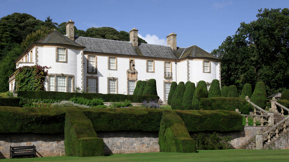 A large white-walled country mansion stands on a slight hill, with stone staircases and terraced gardens leading down in front. Tall trees surround the gardens.