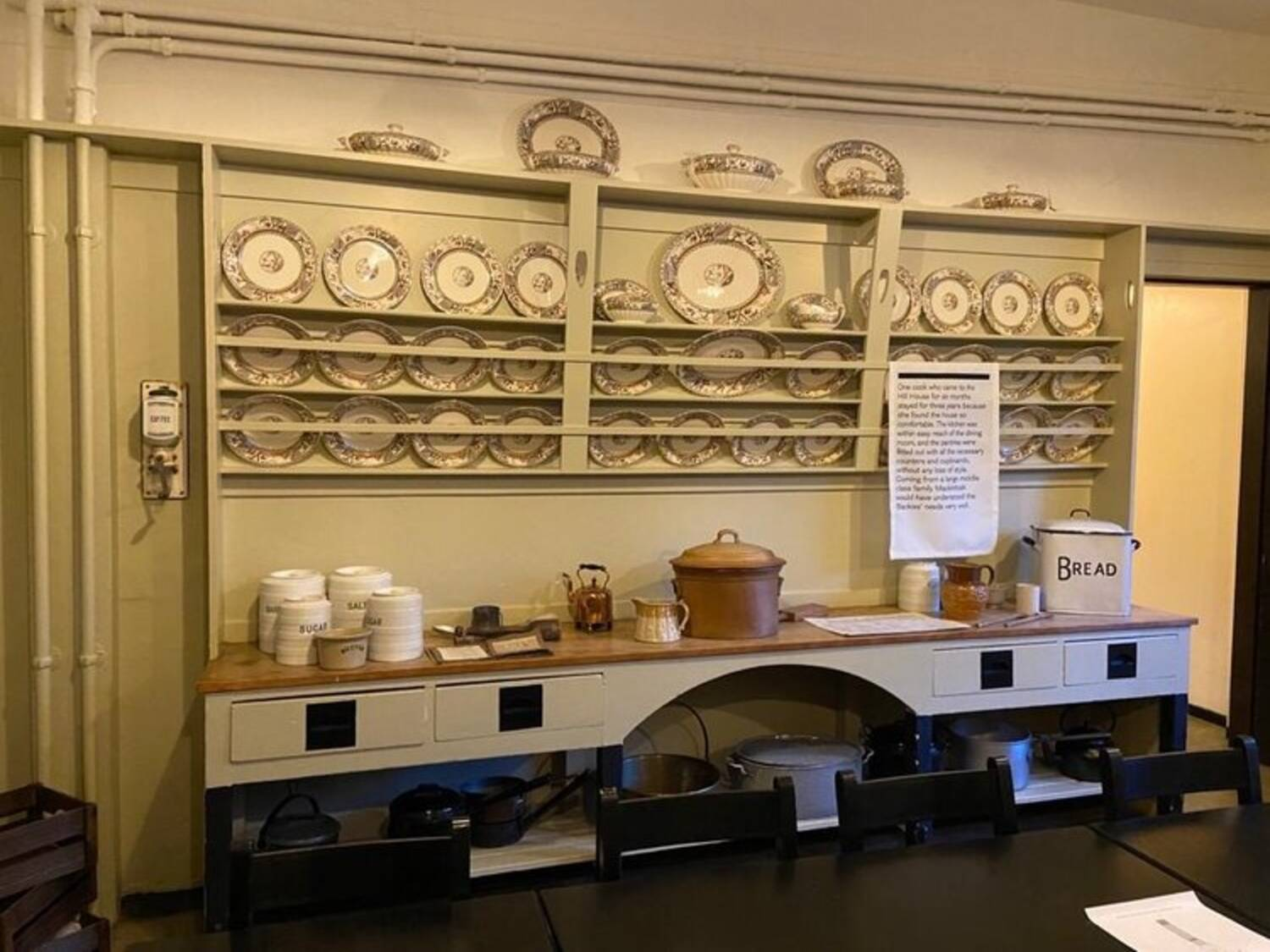 A built-in painted dresser with plates on shelves against the wall. The worktop has boxes and jars on it.