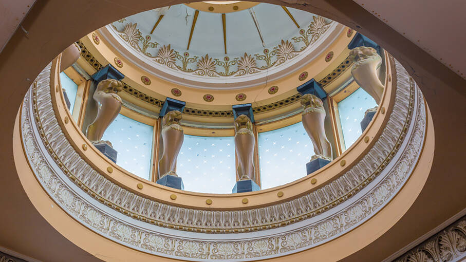 A dome of a house seen from inside. It is beautifully decorated with gold and blue patterns and surrounded by small statues.