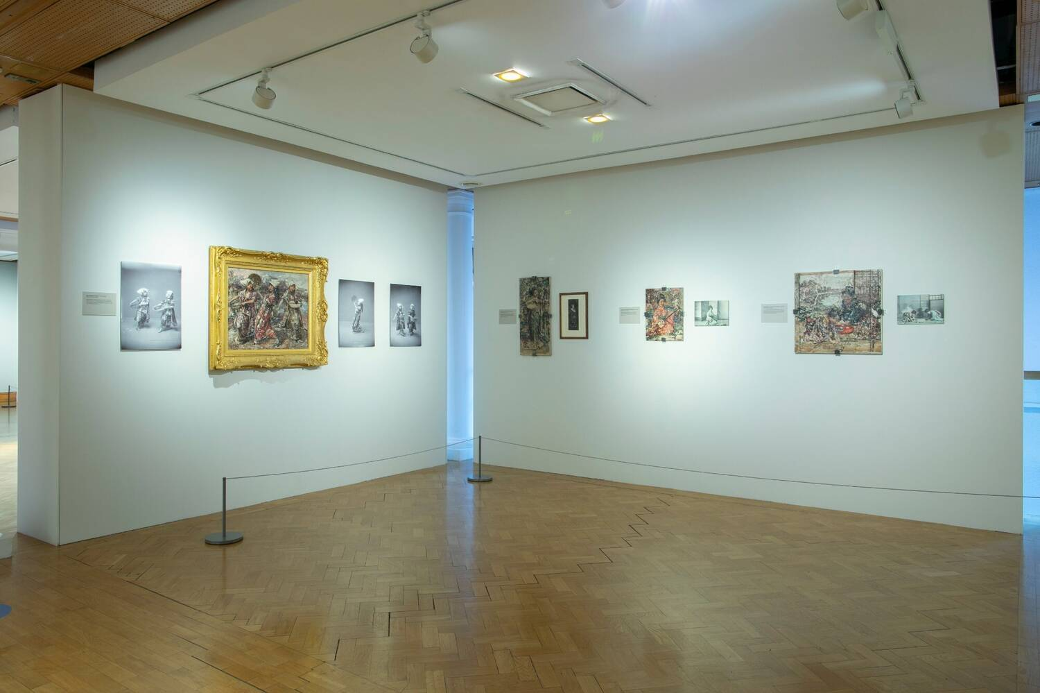 The inside of an art gallery with a wooden parquet floor. Brightly coloured paintings accompanied by a mix of delicately coloured and black and white photos are visible on the white walls.