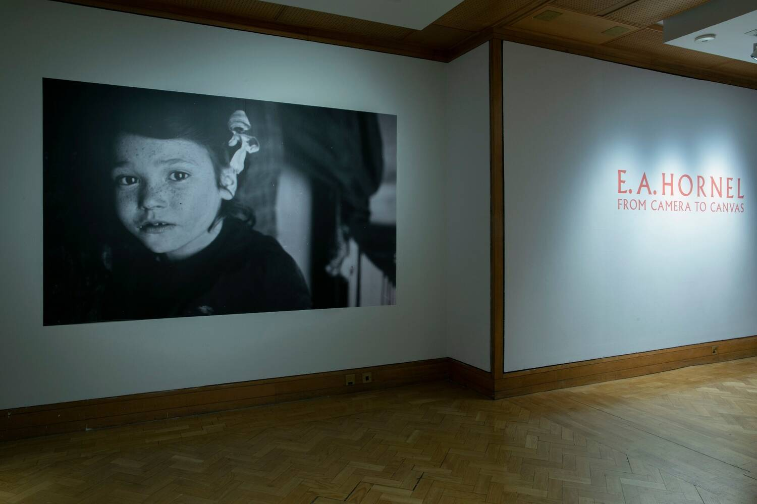 A white wall and wooden parquet floor in a gallery. The left-hand side of the wall is filled with a black and white photo of the bust of a girl staring out at the viewer. On the right-hand side is the text: 'E. A. Hornel: From Camera to Canvas'.