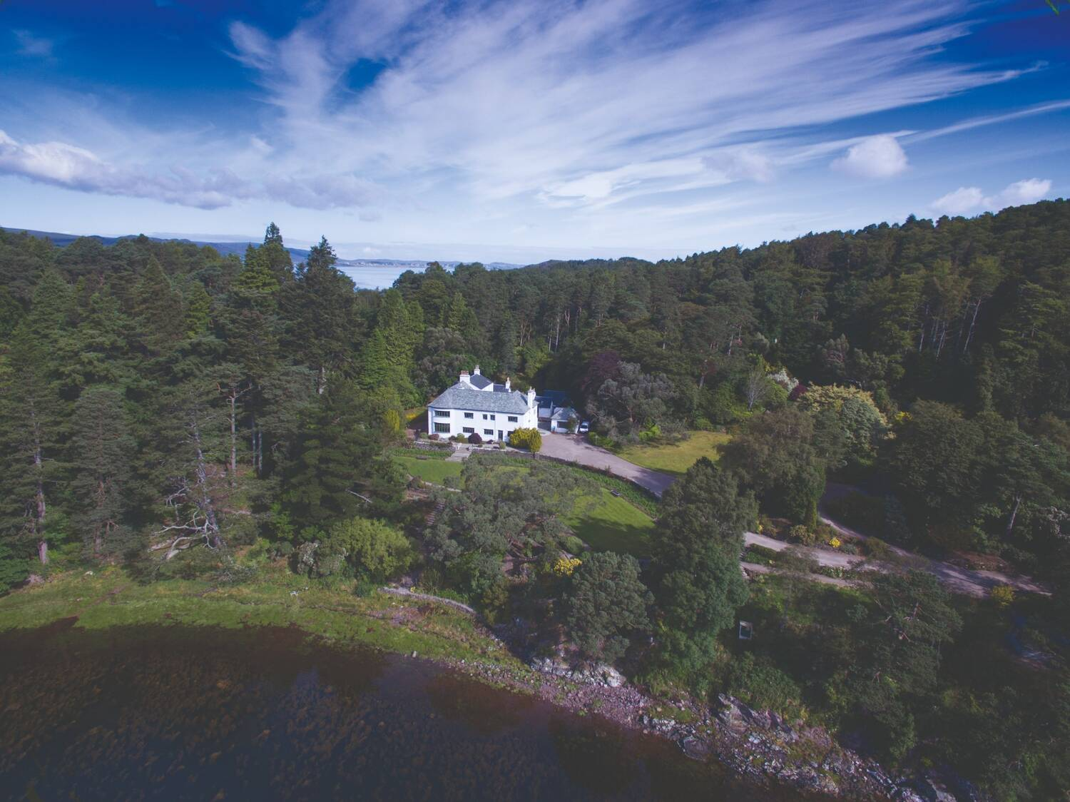 Aerial shot of Inverewe House surrounded by woods and with the shoreline of Loch Ewe.