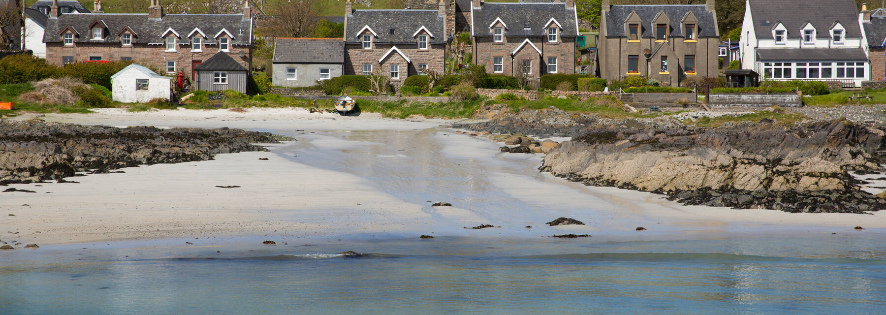 Iona sandy beach with houses and hill in background