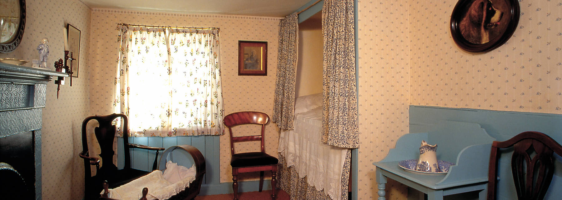 J M Barrie's Birthplace bedroom with cradle and painting of a St Bernard dog