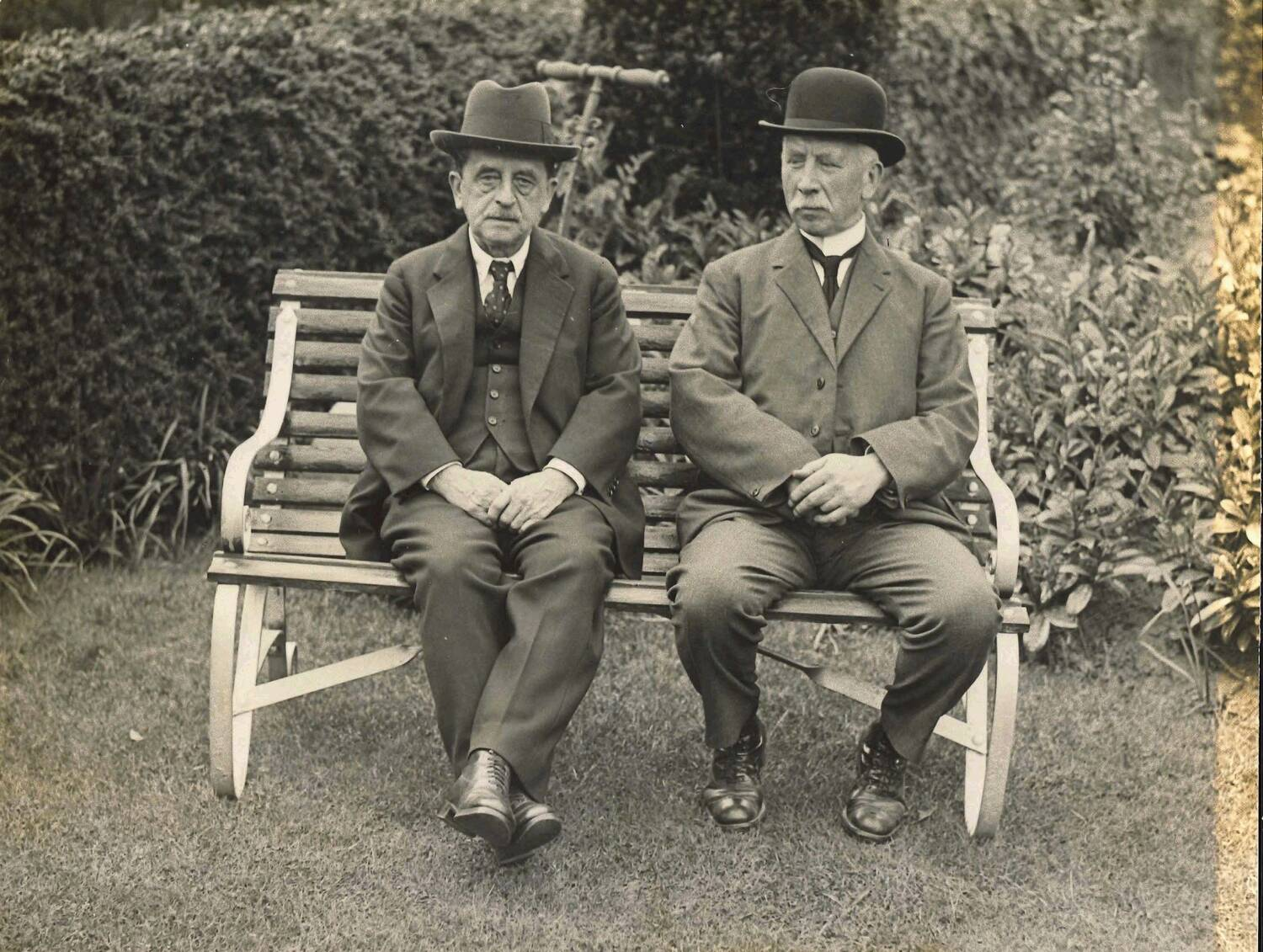 Black and white photograph of two men wearing suits and hats, sitting on a bench in a garden.