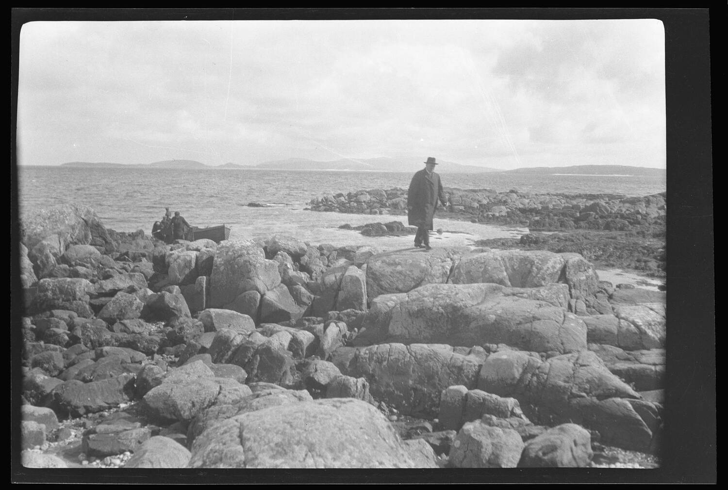 A man in a long coat and dark hat walks across the rocky shore of a far-flung island ...