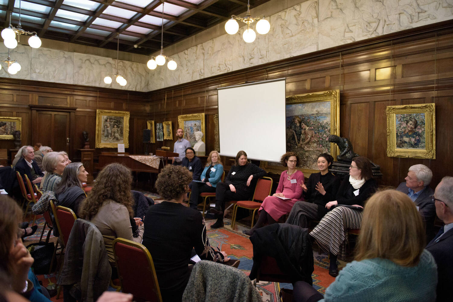 A crowd of people sitting in a wood-panelled room surrounded by paintings. Facing them sit 7 speakers from the symposium.