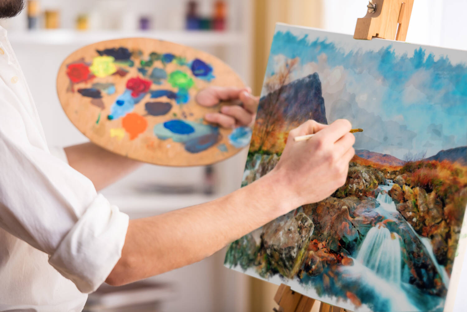 An artist holding a palette full of brightly coloured paint, painting a landscape scene on an easel.