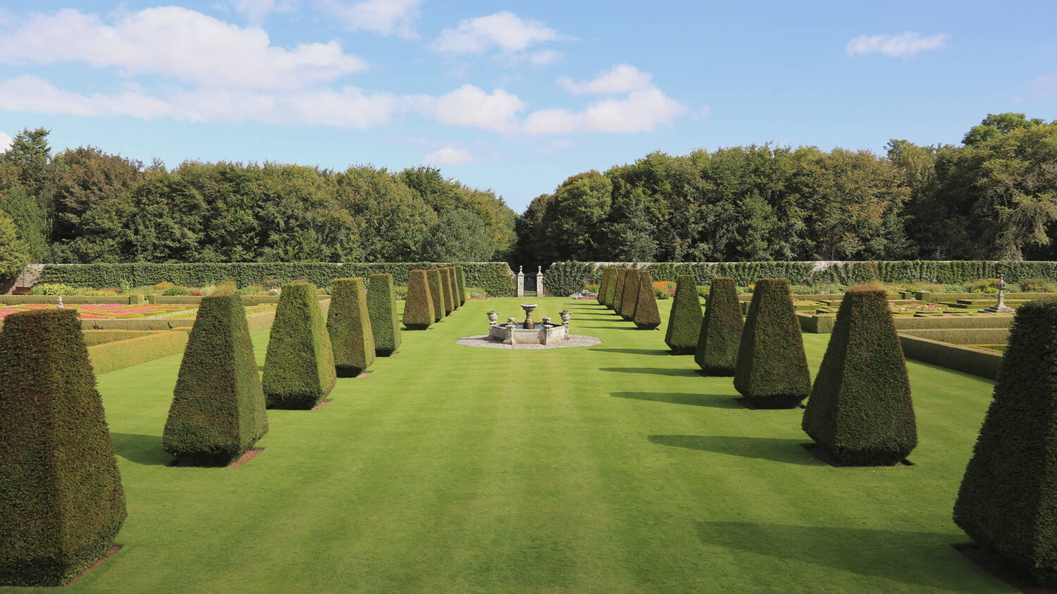 A view of an avenue of clipped yew trees on either side of a manicured lawn. A stone fountain stands at the centre. Woodland can be seen in the distance.