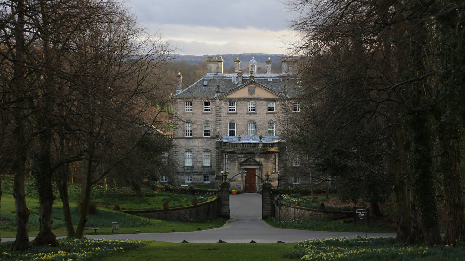 Looking down from the hill towards the front entrance of Pollok House, as the morning sun catches the east of the building. Hosts of daffodils pop out from the ground.