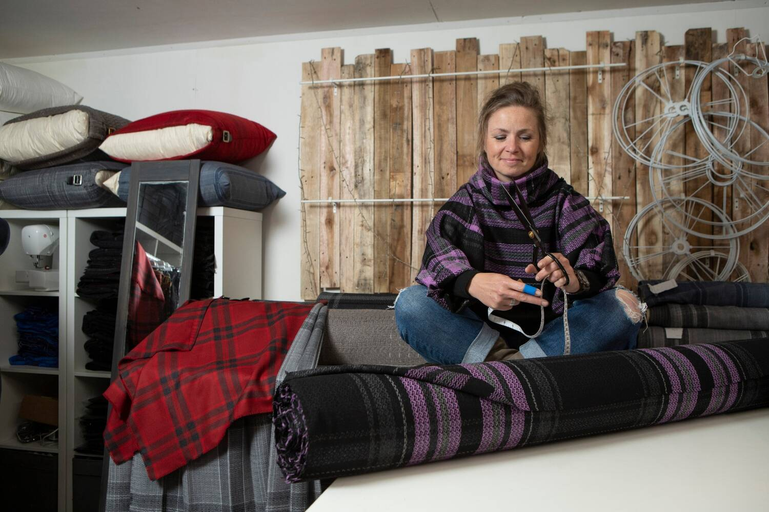 A woman sits cross-legged on the floor with a roll of tartan textile in front of her.