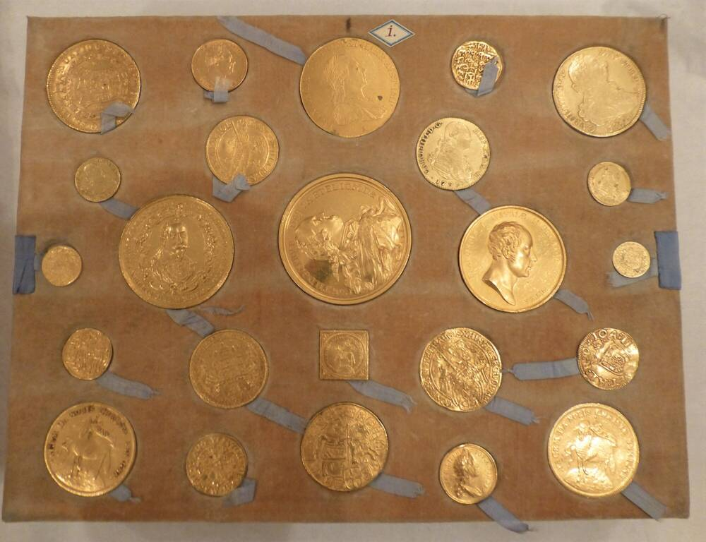 A tray of gold-coloured coins of varying sizes. They are linked by a thin blue ribbon.